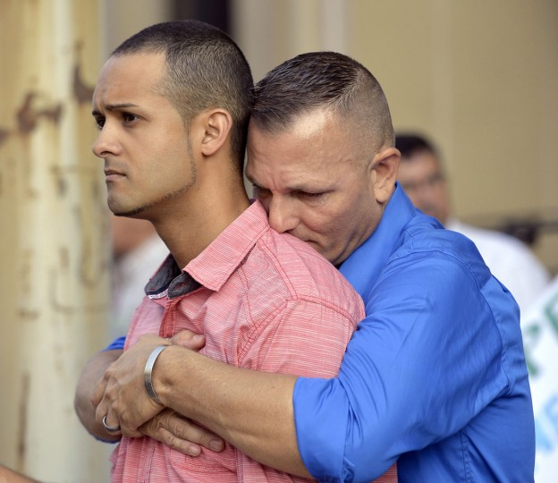 Jonathan Beebe-Franqui, left, and his husband Dwayne D. Beebe-Franqui embrace as they wait for the arrival of Rowan County Clerk Kim Davis at the Carl D. Perkins Federal Building in Ashland, Ky., Thursday, Sept. 3, 2015. Davis has been ordered to appear in Federal Court to explain why she is refusing to issue marriage licenses despite a federal order to do so. (AP Photo/Timothy D. Easley)