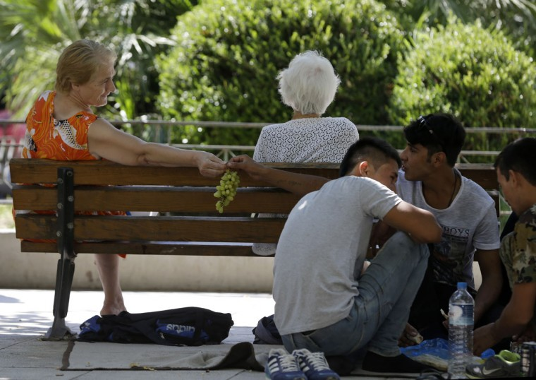 A local resident offers grapes to an Afghan migrant as they sit at Victoria square, Athens, Wednesday, Sept. 2, 2015, where many migrants stay temporarily before continuing their trip to more prosperous European countries. The country has borne the brunt of a massive refugee and migration flow of people heading into the European Union, with more than 200,000 people arriving so far this year. (AP Photo/Thanassis Stavrakis)