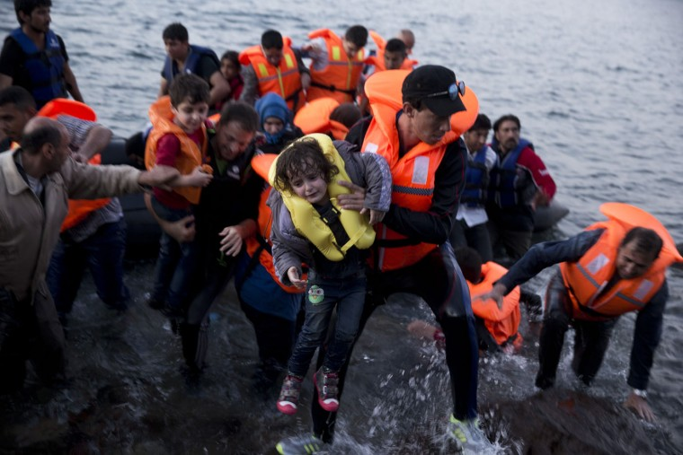 Syrian refugees arrive aboard a dinghy after crossing from Turkey, to the island of Lesbos, Greece, on Sunday, Sept. 20, 2015. A boat with 46 migrants has sunk Sunday in Greece and the coast guard says it is searching for 26 missing off the eastern Aegean island of Lesbos. (AP Photo/Petros Giannakouris)