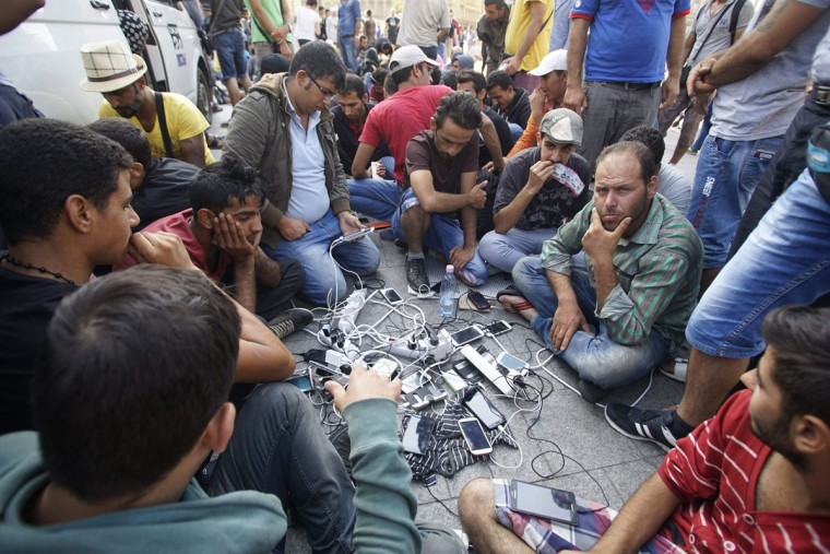 Migrants charge their mobile phones outside the Keleti Railway Station in Budapest, Hungary, Wednesday, Sept. 2, 2015. The station continues to be closed to migrants, other passengers are allowed to enter and trains operate according to schedule. (Zoltan Balogh/MTI via AP)
