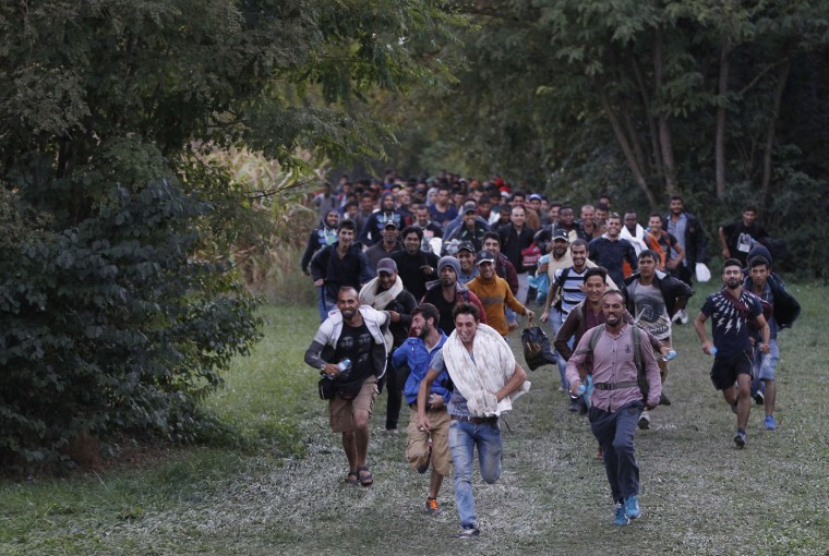 Migrants run as they cross the border from Croatia near the village of Zakany, Hungary, Sunday, Sept. 20, 2015. Croatia said it was overwhelmed by the influx of thousands of people in just a few days and would be sending them to Slovenia and Hungary. (AP Photo/Petr David Josek)
