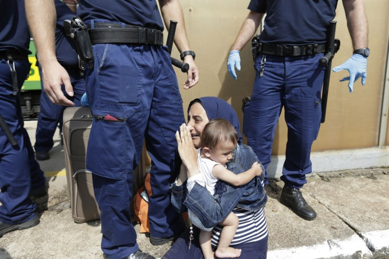 A migrant is detained in Bicske, Hungary, Thursday, Sept. 3, 2015. Over 150,000 migrants have reached Hungary this year, most coming through the southern border with Serbia. Many apply for asylum but quickly try to leave for richer EU countries. (AP Photo/Petr David Josek)