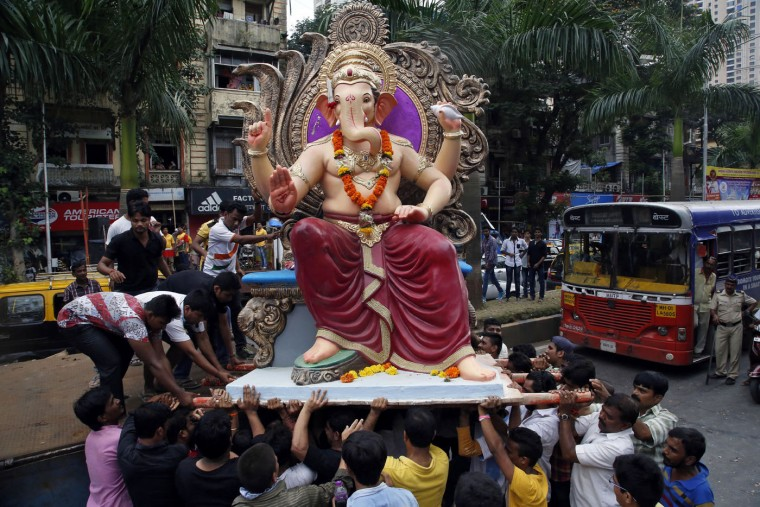 Devotees carry an idol of elephant headed Hindu god Ganesha from a workshop to a worship venue ahead of the Ganesh Chaturthi festival in Mumbai, India, Sunday, Sept. 13, 2015. After worshipping during the ten day long festival, the idol will be immersed in the Arabian Sea. (AP Photo/Rajanish Kakade)