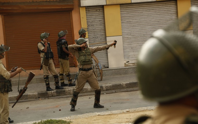 A paramilitary soldier aims his sling shot at Kashmiri protesters in Srinagar, Indian controlled Kashmir Sunday, Sept. 20, 2015. Kashmiri separatists called for a strike to protest Saturday's killing of a 3-year-old boy and his father in Indian-controlled Kashmir. (AP Photo/Mukhtar Khan)
