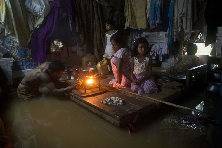 A man lights a stove to make food as his family members take shelter on a bed after flood waters enter their house following heavy monsoon rains in Gauhati, India , Wednesday, Sept. 23, 2015. India receives its monsoon rains from June to September. (AP Photo/Anupam Nath)