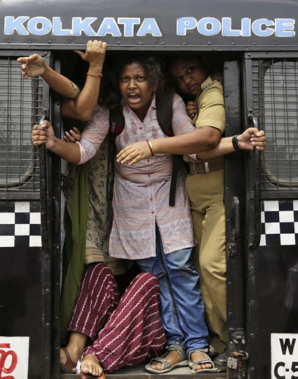 An activist of Socialist Unity Center of India shouts slogans as she is detained by the police in a van during a daylong nationwide strike called by the trade unions in Kolkata, India, Wednesday, Sept. 2, 2015. Normal life was affected in various parts of the country, including the West Bengal state, as central trade unions on Wednesday went on a day-long nationwide strike to protest against changes in labour laws and privatisation of Public Sector Undertakingís (PSU), a government owned corportation. (AP Photo/Bikas Das)