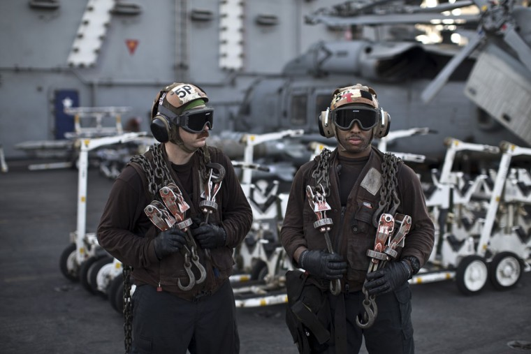 U.S. Navy air wing plane captains carry chains as they pause on the flight deck of the USS Theodore Roosevelt aircraft carrier. Plane captains are identified by wearing brown shirts and are responsible for preparing the aircraft for flight. Every day, the steam-powered catapult aboard this massive aircraft carrier flings American fighter jets into the sky, on missions to target the extremist Islamic State group in Iraq and Syria.(AP Photo/Marko Drobnjakovic)