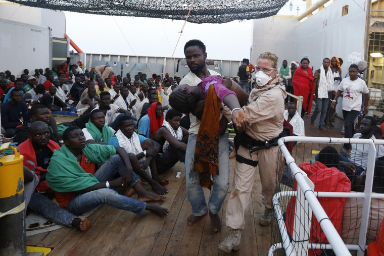Norwegian Police officers, Lillian Berg, right, helped by a migrant carries a fainted woman on bridge of the Norwegian Siem Pilot ship, Wednesday, Sept. 2, 2015. The Siem Pilot is carrying to the Italian Port of Cagliari hundreds of migrants rescued in several operations in the Mediterranean sea. (AP Photo/Gregorio Borgia)