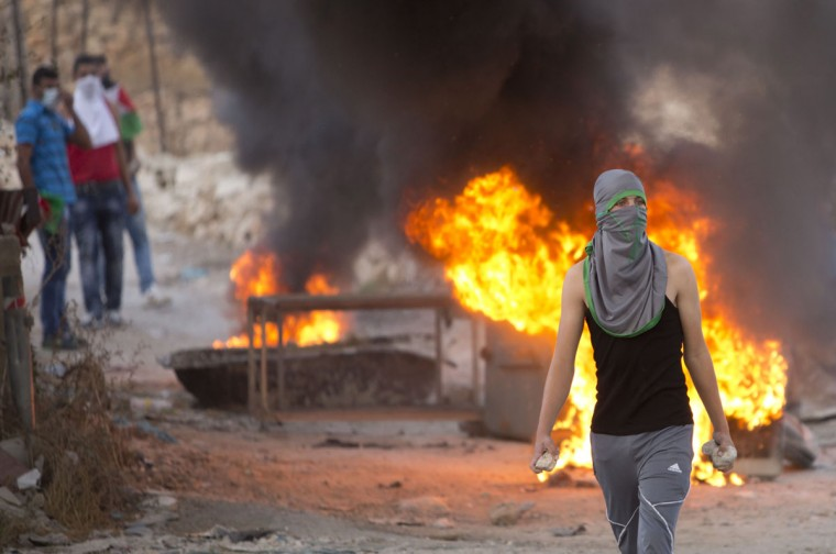 A Palestinian demonstrator holds rocks during clashes with Israeli security forces, at Hizme checkpoint near the West Bank city of Ramallah, Wednesday, Sept. 30, 2015, as Palestinian President Mahmoud Abbas addressed the UN General Assembly and declared that he is no longer bound by agreements signed with Israel. (AP Photo/Majdi Mohammed)