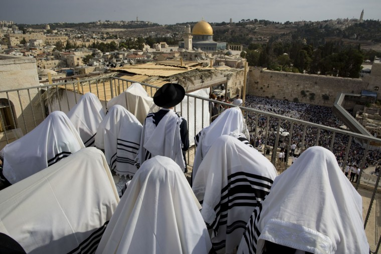 Covered in prayer shawls, Jewish men of the Cohanim Priestly caste participate in a blessing during the holiday of Sukkot, in front of the Western Wall, the holiest site where Jews can pray in Jerusalem's Old City, Wednesday, Sept. 30, 2015. The Cohanim, believed to be descendants of priests who served God in the Jewish Temple before it was destroyed, perform a blessing ceremony of the Jewish people three times a year during the festivals of Passover, Shavuot and Sukkot. (AP Photo/Oded Balilty)
