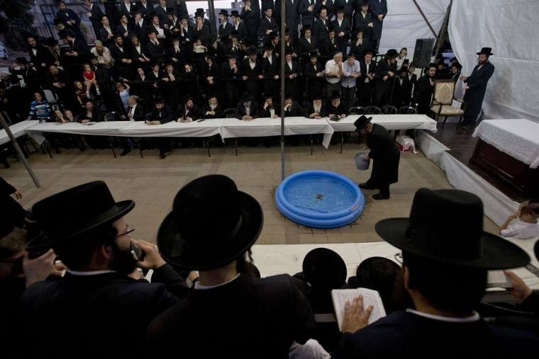 "Ultra-Orthodox Jewish men surround a portable swimming pool with goldfish as they participate in a Tashlich ceremony in the ultra-Orthodox city of Bnei Brak , near Tel Aviv, Israel, Sunday, Sept. 20, 2015. Tashlich, which means ""to cast away"" in Hebrew, is the practice in which Jews go to a large flowing body of water and symbolically ""throw away"" their sins by throwing a piece of bread, or similar food, into the water before the Jewish holiday of Yom Kippur, which starts at sundown Tuesday. (AP Photo/Ariel Schalit)"
