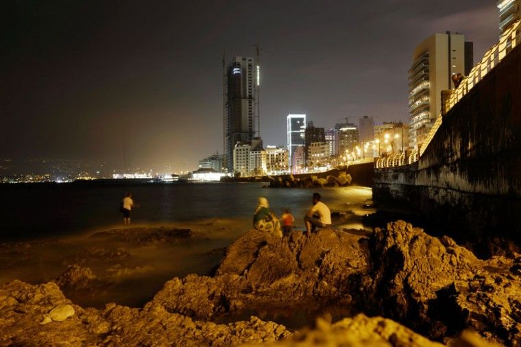 In this picture taken late Monday, Sept. 14, 2015, people look out to the Mediterranean Sea as a Lebanese angler casts a fishing pole from a rocky coastal area in Beirut, Lebanon. (AP Photo/Hassan Ammar)