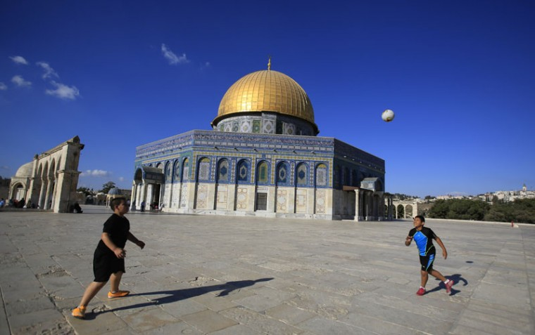Palestinian boys play ball near the Dome of the Rock Mosque in the Al-Aqsa Mosque compound in Jerusalem's Old City, Monday, Aug. 31, 2015. (AP Photo/Hatem Moussa)