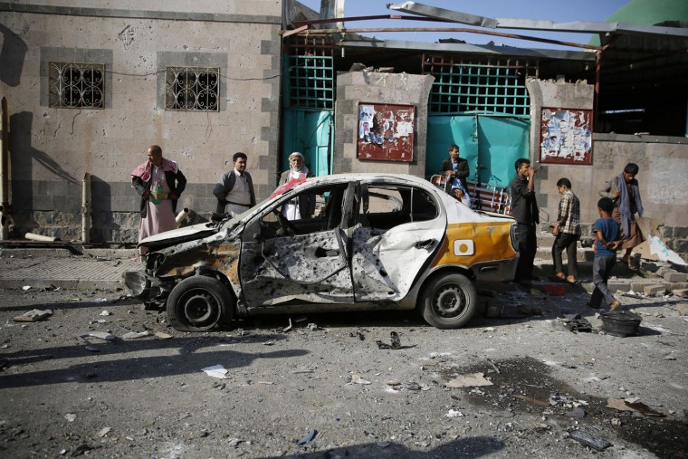 People gather at the site of a car bomb attack next to a Shiite mosque in Sanaa, Yemen, Thursday, Sept. 3, 2015. An Islamic State-claimed suicide bomber and a subsequent car bombing killed at least 20 people Wednesday at a mosque in Yemen's rebel-held capital, Sanaa, amid the country's raging civil war, officials said. (AP Photo/Hani Mohammed)