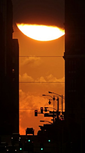 The sun dips behind a cloud as it rises between tall buildings in downtown Kansas City, Mo. Wednesday, Sept. 23, 2015. Today marked the autumnal equinox or the beginning of fall in which day and night are balanced to about 12 hours each. (AP Photo/Charlie Riedel)