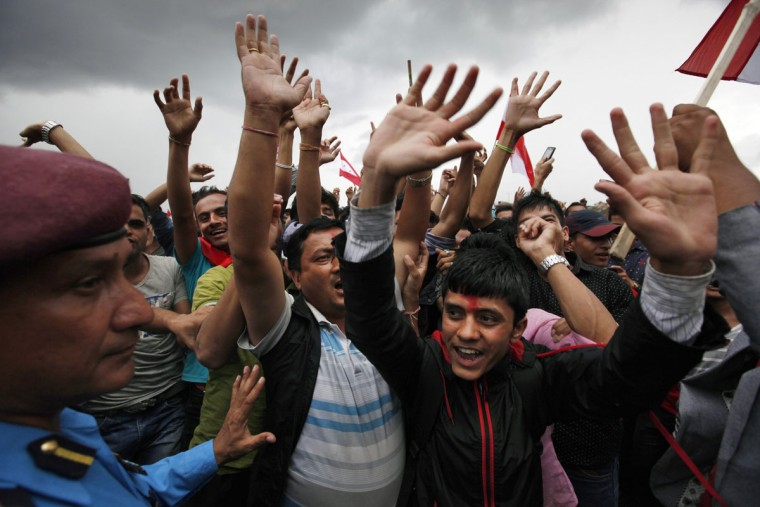 Nepalese people cheer as they attend a function held to celebrate the adoption of the country's new constitution in Kathmandu, Nepal, Monday, Sept. 21, 2015. Nepal on Sunday, Sept. 20, 2015, formally adopted a much anticipated and long-delayed constitution that took more than seven years to complete following a decade of political infighting. (AP Photo/Niranjan Shrestha)
