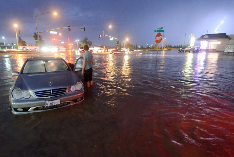 A motorist stands in water near Bear Valley Outerhighway South, Tuesday, Sept. 8, 2015, in Hesperia, Calif. The National Weather Service issued a flash flood warning and severe thunderstorm warning for the area on Tuesday night. (David Pardo/The Victor Valley Daily Press via AP)
