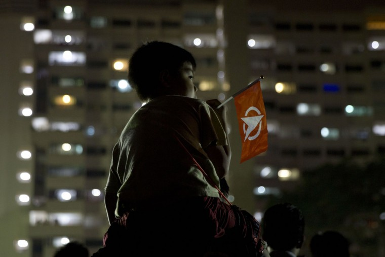A child holds the flag for the opposition Singapore Democratic Party during a final rally before the Sept. 11 general elections in Singapore, Wednesday, Sept. 9, 2015. For the first time in Singapore's history, opposition parties are contesting all 89 seats at stake. (AP Photo/Ng Han Guan)