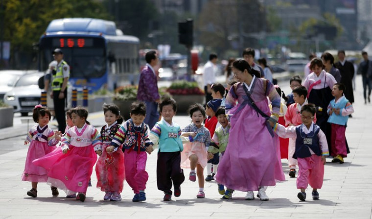 "Children wearing South Korea's traditional costume ""Hanbok"" walk together hand in hand during a street campaign to encourage people to wear ""Hanbok"" for the upcoming country's holiday, Chuseok, the Korean version of Thanksgiving Day, which falls on Sept. 27, in Seoul, South Korea, Thursday, Sept. 24, 2015. South Koreans will visit their hometowns during the four-day holiday starting on Saturday. (AP Photo/Lee Jin-man)"