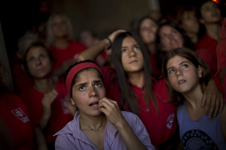 "Members of different Castellers watch as ""Joves Xiquets de Valls"" form a human tower or ""Castellers"" during the Saint Merce celebrations in San Jaime square in Barcelona, Spain, Sunday, Sept. 20, 2015. The tradition of building human towers or ""castells"" dates back to the 18th century and takes place during festivals in Catalonia, where ""colles"" or teams compete to build the tallest and most complicated towers. A ""castell"" is considered completely successful when it is loaded and unloaded without falling apart. In 2010 ""castells"" were declared by UNESCO one of the Masterpieces of the Oral and Intangible Heritage of Humanity. (AP Photo/Emilio Morenatti)"