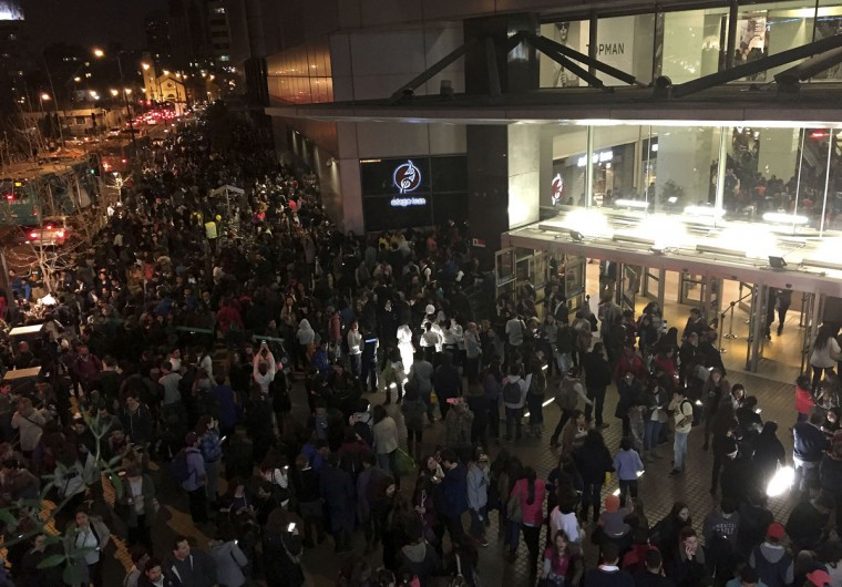 People evacuate a mall in Santiago after a powerful earthquake, in Santiago, Chile, Wednesday, Sept. 16, 2015. The magnitude-8.3 earthquake hit off Chile's northern coast causing buildings to sway in Santiago and other cities and sending people running into the streets. Authorities reported one death in a town north of the capital. (Nadia Perez/AGENCIA UNO via AP)