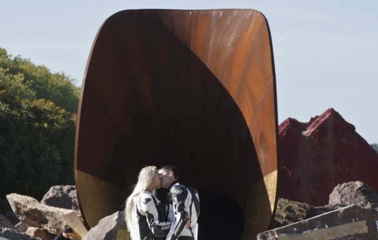 "A couple kiss next to the sculpture ""Dirty Corner"", by British-Indian artist Anish Kapoor, in the gardens of the Chateau de Versailles, Monday, Sept. 28, 2015 in Versailles, west of Paris, France. The Chateau de Versailles welcomes the English artist Anish Kapoor for a major contemporary art exhibition in the gardens. The exhibition lasts until Nov. 1, 2015. (AP Photo/Michel Euler)"