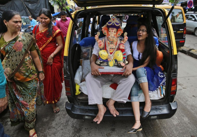 Indian devotees carry an idol of elephant-headed Hindu God Ganesha in the trunk of a taxi during Ganesh Chaturthi festival celebrations in Mumbai, India, Thursday, Sept. 17, 2015. The 10-day long Ganesh festival began Thursday and ends with the immersion of Ganesha idols in water bodies on the 10th day. (AP Photo/Rafiq Maqbool)