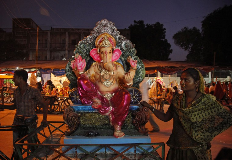 An Indian woman carries an idol of elephant-headed Hindu God Ganesha on a cycle cart for sale on the eve of Ganesh Chaturthi festival in Ahmadabad, India, Wednesday, Sept. 16, 2015. Ganesh Chaturthi, celebrated as the birthday of Lord Ganesha, begins Sept. 17. The idols will be immersed in water bodies at the end of the 10-day festival. (AP Photo/Ajit Solanki)