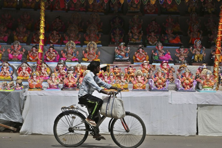 A cyclist rides past rows of idols of elephant headed Hindu god Ganesh displayed for sale in Bangalore, India, Sunday, Sept. 13, 2015. The idols are in demand ahead of the Ganesh Chaturthi festival that celebrates the birthday of Lord Ganesha. (AP Photo/Aijaz Rahi)