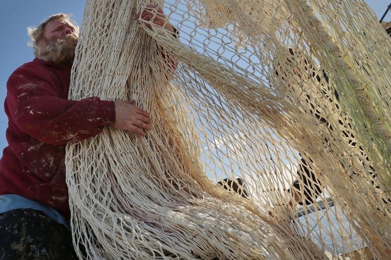 John Gatcombe, a deckhand aboard the fishing vessel Voyager, gathers a huge herring net, as he loads it onto the back of a truck in New Bedford, Mass. In the mid-1800s, the city was the undisputed hub of the global whaling industry, when it existed. The commercial fishing industry remains viable, but not as lucrative as in earlier times. (Peter Pereira/The Standard-Times via AP)