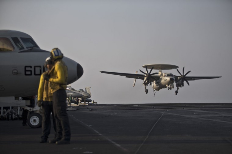 Plane Directors, wearing yellow jerseys, stand back as a U.S. Navy aircraft lands on the USS Theodore Roosevelt aircraft carrier in the Persian Gulf. Every day, the steam-powered catapult aboard this massive aircraft carrier flings American fighter jets into the sky, on missions to target the extremist Islamic State group in Iraq and Syria.(AP Photo/Marko Drobnjakovic)
