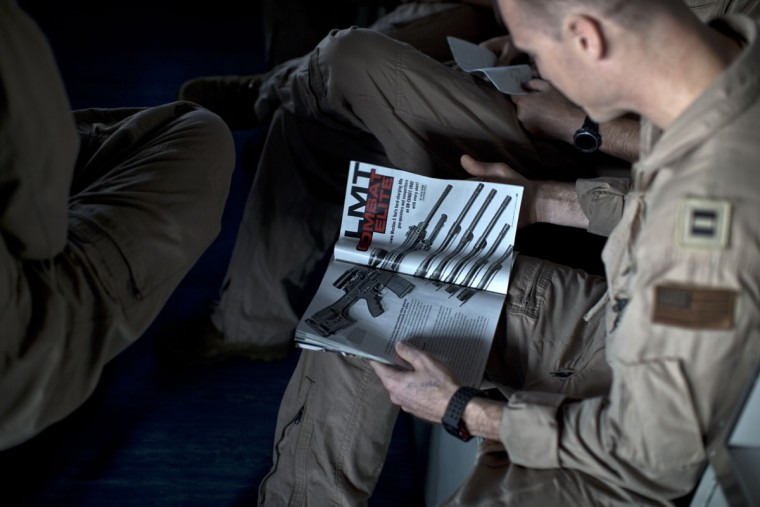 A U.S. Navy pilot reads a specialized weapons magazine as he sits on board the USS Theodore Roosevelt, a Nimitz class nuclear powered aircraft carrier currently deployed in the Persian Gulf, supporting Operation Inherent Resolve, the military operation against Islamic State extremists in Syria and Iraq. Below deck is a complex set of passageways and tunnels, hangars and sailorsí quarters, gyms and mess halls, engine rooms and offices. Painted murals bear fighter squadron insignia, U.S. flags, the cartoon figure Popeye and other patriotic imagery. (AP Photo/Marko Drobnjakovic)
