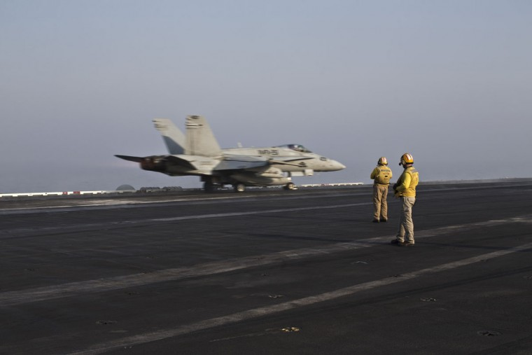Plane directors, wearing yellow jerseys, oversee the takeoff of a U.S. Marine fighter jet aircraft aboard the USS Theodore Roosevelt aircraft carrier. Pilots onboard have flown missions into both Iraq and Syria, part of the over 6,800 airstrikes carried out since August 2014. Some 20 percent of all coalition strikes come from aircraft launched from the nuclear-powered Roosevelt.(AP Photo/Marko Drobnjakovic)