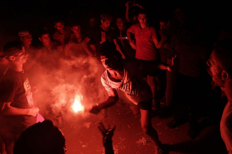 "In this Saturday, Sept. 26, 2015 photo, boys dance with flares during a wedding in Al Omraniayah, a suburb on the outskirts of Cairo. Since the 2011 uprising, the music of ""Mahraganat,"" Arabic for ""festivals,"" has emerged from and spread through impoverished communities, where local musicians play, especially during weddings, their auto-tuned beats and songs that tackle social, political and cultural issues. (AP Photo/Amr Nabil)"