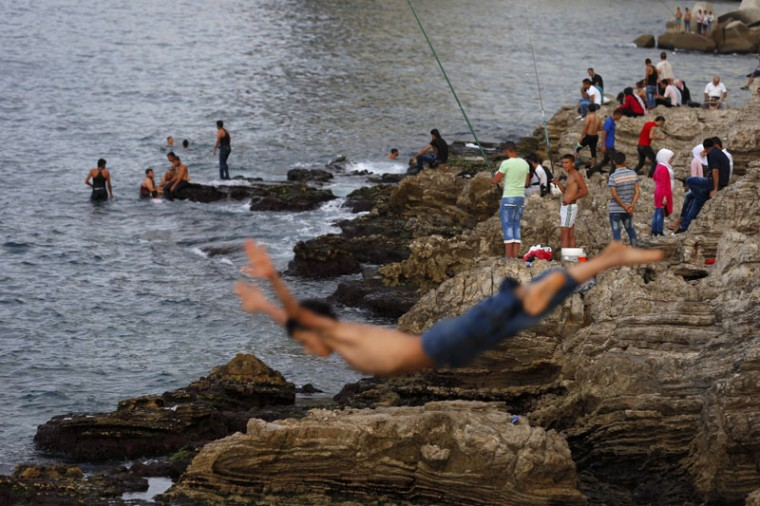 A man jumps into the Mediterranean Sea as Lebanese anglers cast their fishing poles from a rocky coastal area on the Beirut coastline, Lebanon, Sunday, Sept. 27, 2015. (AP Photo/Hassan Ammar)