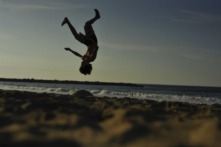 A young boy jumps over the sand of the beach while the sun sets, in San Sebastian, northern Spain, Saturday, Sept. 26, 2015.(AP Photo/Alvaro Barrientos)