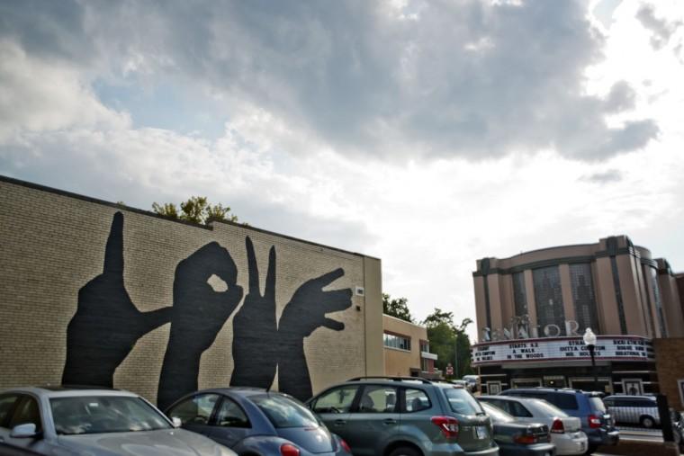 "A mural showcasing hands that spell the word ""love"" adorn a building near The Senator. (Emma Patti Harris/Baltimore Sun)"