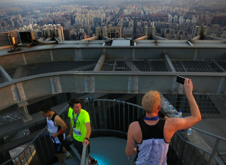People take photos of the Beijing skyline from the top of the China World Trade Center Tower 3 at sunset after competing in the China Vertical Run, a race up the building's steps, Saturday, Sept. 19, 2015. The 330-meter (1,083 foot) tower is the tallest building in Beijing, and though the city is notorious for its air pollution, an extended run of mostly clear days afforded a good view of the city on Saturday. (Mark Schiefelbein/Associated Press)