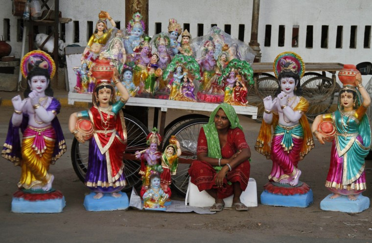 An Indian woman sit amid Idols of Hindu Lord Krishna and his consort Radha displayed for sale on the eve of Janmashtami in Ahmadabad, India, Friday, Sept. 4, 2015. Janmashtami is the festival that marks the birth of Krishna. (AP Photo/Ajit Solanki)