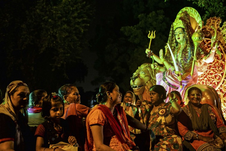 Indian women sit on a chariot with a statue of the Hindu goddess Durga during a procession marking the Hindu festival of Janmashtami, in New Delhi on September 1, 2015. (Chandan Khanna/AFP/Getty Images)