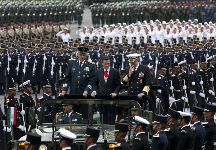 Flanked by his Secretary of Defense Gen. Salvador Cienfuegos Zepeda, left, and Secretary of the Navy Adm. Vidal Soberon Sanz, right, Mexico's President Enrique Pena Nieto rides in an open military vehicle during the Independence Day military parade in the capital's main plaza, the Zocalo, in Mexico City, Wednesday, Sept. 16, 2015. Mexico celebrates the anniversary of its 1810 independence uprising. (AP Photo/Marco Ugarte)