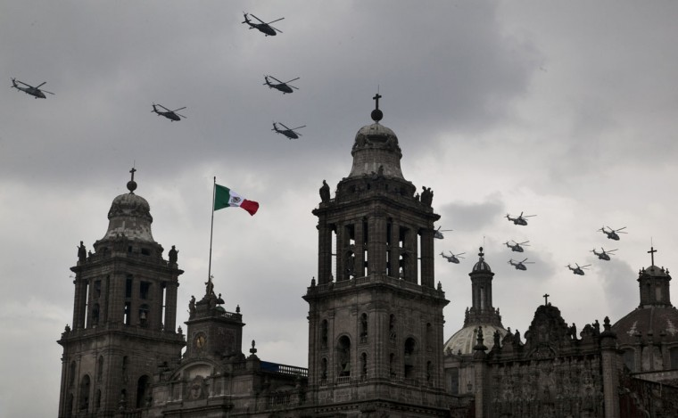Army helicopters fly over the Metropolitan Cathedral during the Independence Day military parade in the capital's main plaza, the Zocalo, in Mexico City, Wednesday, Sept. 16, 2015. Mexico celebrates the anniversary of its 1810 independence uprising. (AP Photo/Marco Ugarte)