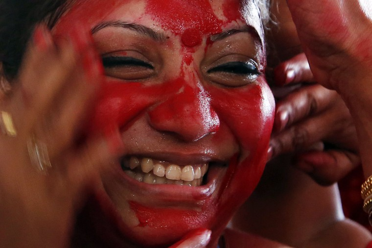 An Indian woman smiles as others apply vermillion paste on her face during celebrations marking Durga Puja festival in Mumbai, India, Thursday, Oct. 22, 2015. The festival commemorates the slaying of a demon king by lion-riding, 10-armed goddess Durga, marking the triumph of good over evil. (AP Photo/Rajanish Kakade)