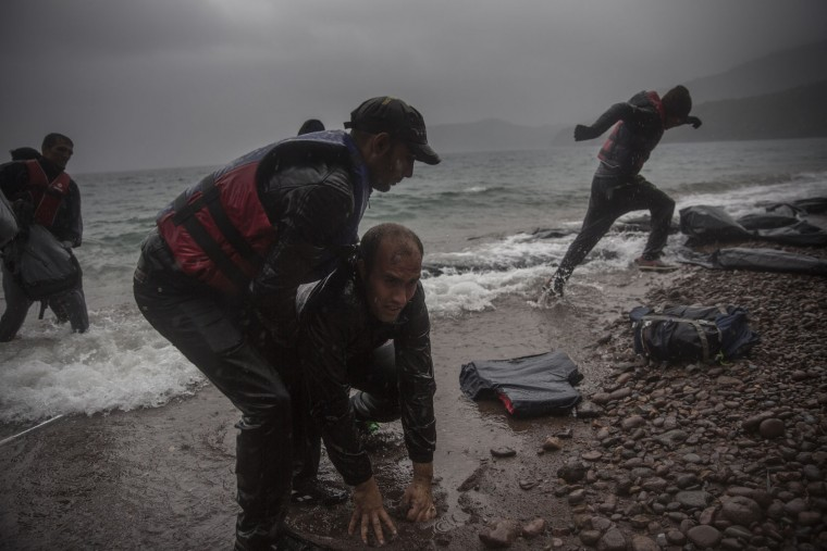 Migrants disembark on a beach after arriving on a dinghy from the Turkish coast to Skala Sikaminias village on the northeastern Greek island of Lesbos, Thursday, Oct. 22, 2015. Greece is the main entry point for those fleeing violence at home and seeking a better life in the European Union. More than 500,000 people have arrived so far this year on Greece's eastern islands, paying smugglers to ferry them across from nearby Turkey. (AP Photo/Santi Palacios)