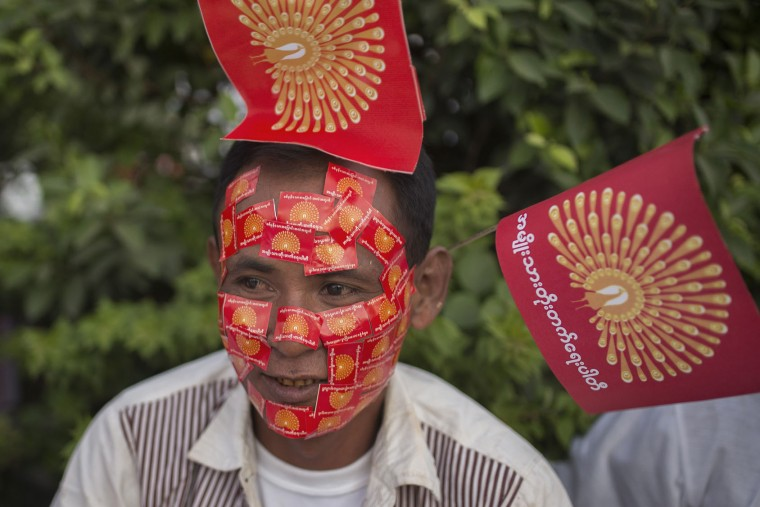 A supporter of National Development Party (NDP) displays stickers of party flags stuck to their face during an election campaign in Mandalay, Myanmar, Sunday, Oct. 25, 2015. Myanmar's general elections are scheduled for November 8, 2015, the first since a nominally civilian government was installed in 2011. (AP Photo/Hkun Lat)