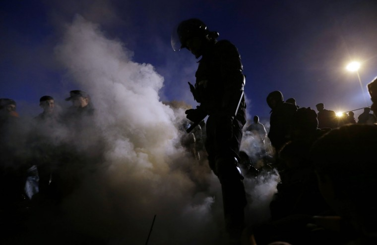 A Slovenian policeman extinguishes fire that migrants were using to warm themselves while waiting to enter a camp in Spielfeld, Austria, Sunday, Oct. 25, 2015. Thousands of people are trying to reach central and northern Europe via the Balkans but often have to wait for days in mud and rain at the Serbian, Croatian and Slovenian borders. (AP Photo/Petr David Josek)