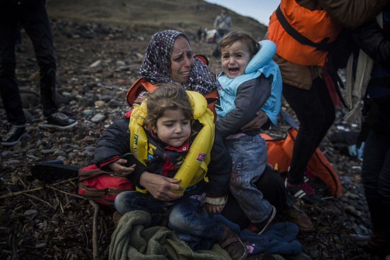 A woman holds two children on a beach after arriving on a dinghy from a Turkish coast to the northeastern Greek island of Lesbos, Sunday, Oct. 25, 2015. The International Office for Migration says Greece over the last week experienced the largest single weekly influx of migrants and refugees this year, at an average of some 9,600 per day. (AP Photo/Santi Palacios)