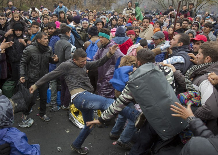 Migrants scuffle as they wait to cross to Austria, in Sentilj, Slovenia, Thursday, Oct. 29, 2015. Asylum-seekers hoping to reach Western Europe turned to crossing Slovenia after Hungary closed its border with Croatia with a barbed-wire fence. (AP Photo/Darko Bandic)