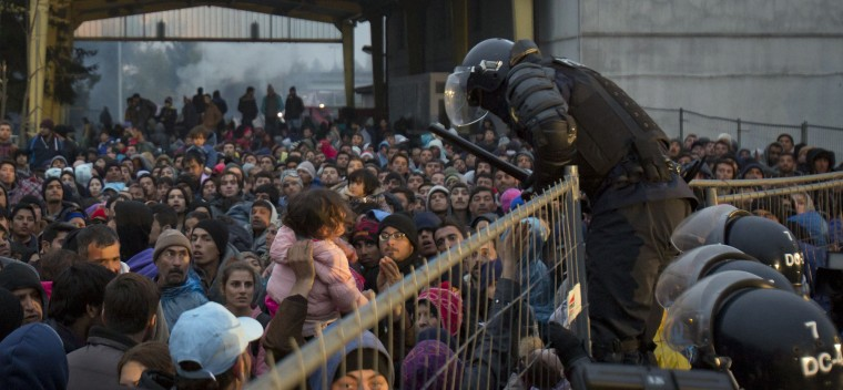 Slovenian police try to control migrants as they cue to enter Austria in Sentilj, Slovenia, Thursday, Oct. 29, 2015. Asylum-seekers hoping to reach Western Europe turned to crossing Slovenia after Hungary closed its border with Croatia with a barbed-wire fence. (AP Photo/Darko Bandic)