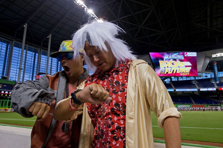 """Fans Luis Carrera (l) and Thomas Chase (r), dressed as Marty McFly and """"Doc"""" Emmett Brown from the movie ''Back to the Future,'' pose for a photo before the game between the Miami Marlins and the Atlanta Braves at Marlins Park on September 25, 2015 in Miami, Florida. (Photo by Rob Foldy/Getty Images)"""